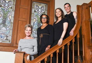 From left, owner Tina Lovelace, lead massage therapist Alex Laub, concierge Tori Tong and concierge Shanice Bergstrand smile from the staircase to the second floor at The Denver Woodhouse Day Spa.