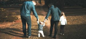 Family walking down a dirt trail.